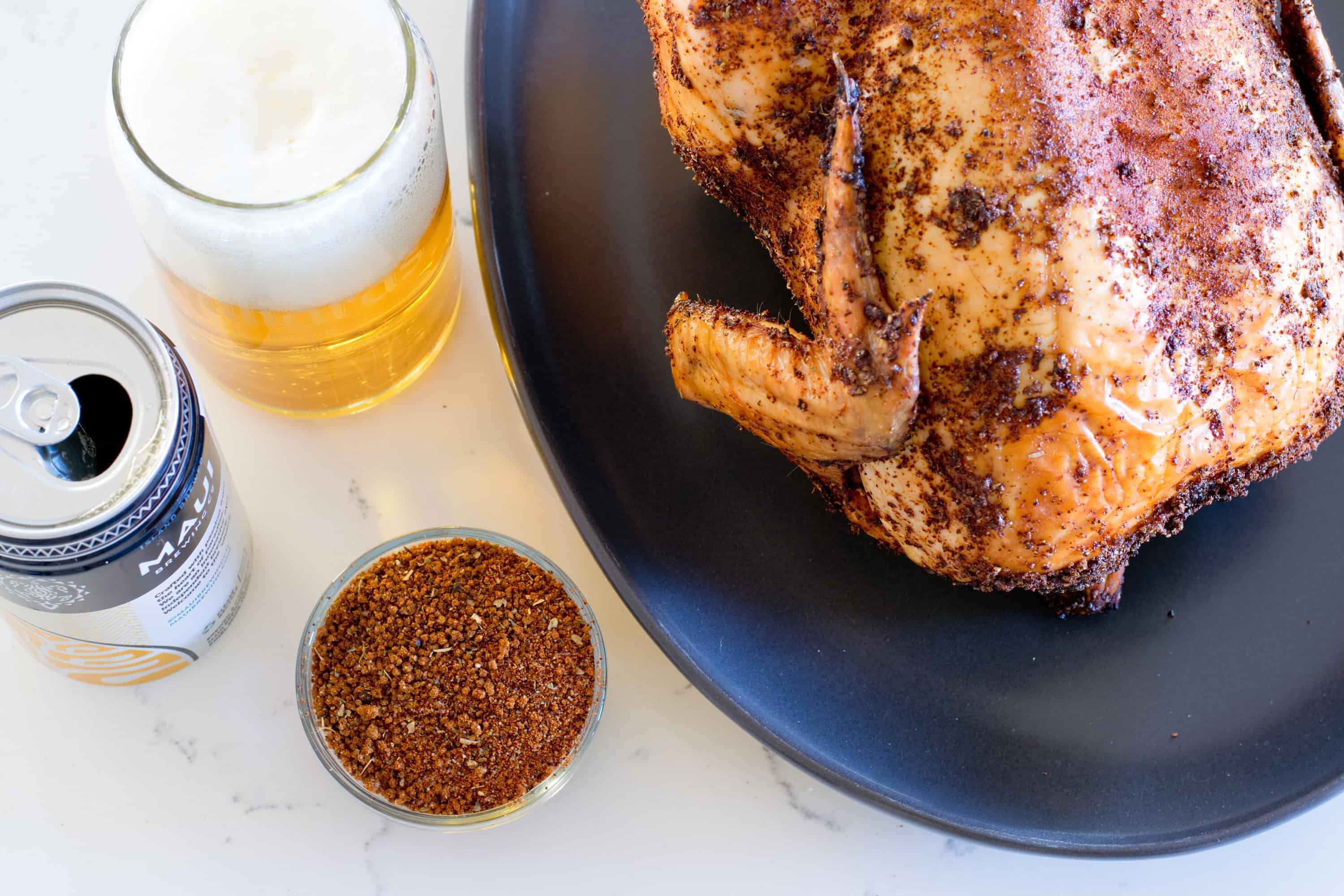 awesome beer can chicken on a dark platter next to a glass and can of beer.