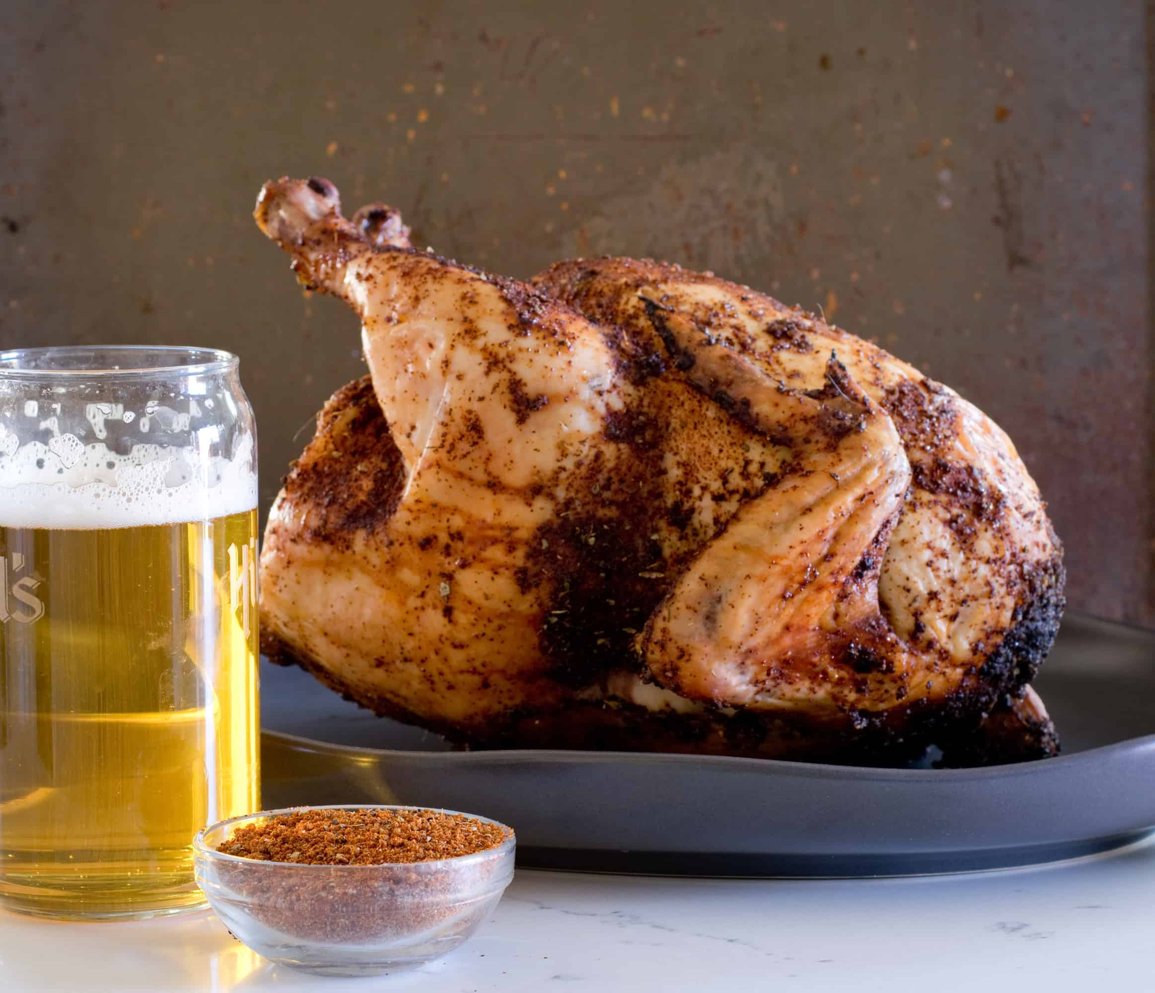 golden brown whole roasted chicken on a dark background next to a glass of beer