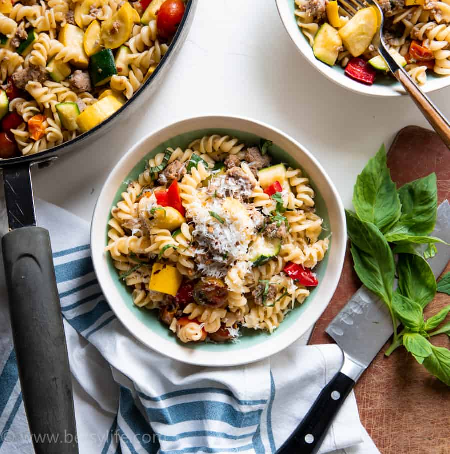 Bowl of turkey sausage pasta primavera next to a skillet and a cutting board with fresh basil