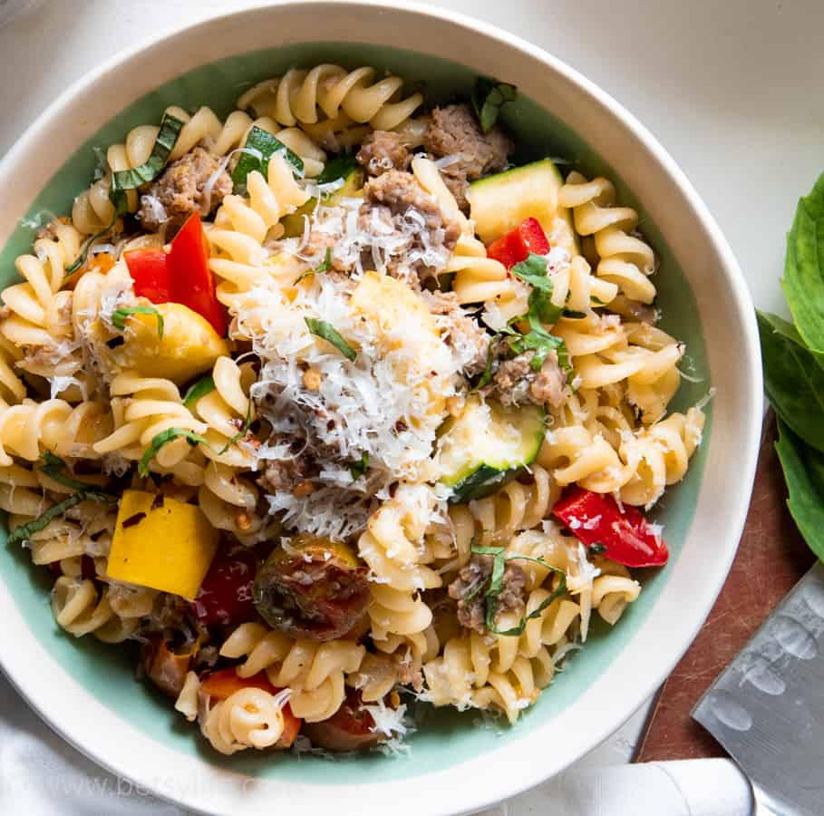 close up of bowl of turkey sausage pasta primavera with grated parmesan on top