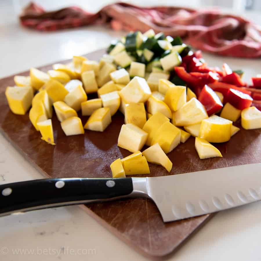 cutting board with chopped yellow squash, zucchini and bell pepper