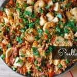 bowl of shrimp paella with green garnish