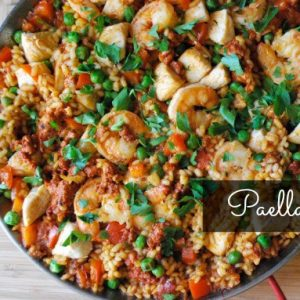 bowl of shrimp paella with green garnish