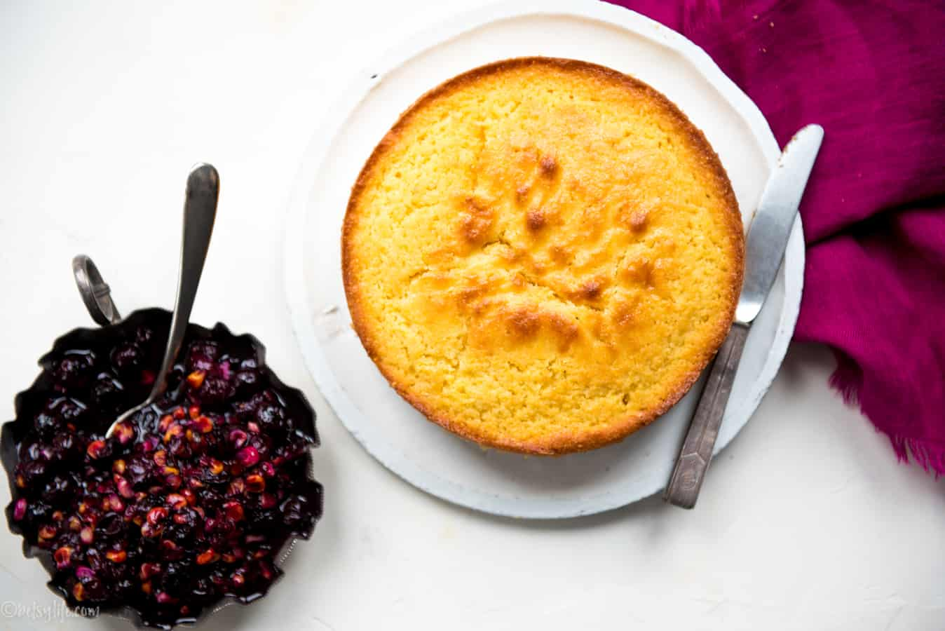 Round corn cake on a white plate next to a metal dish filled with corn & blueberry compote