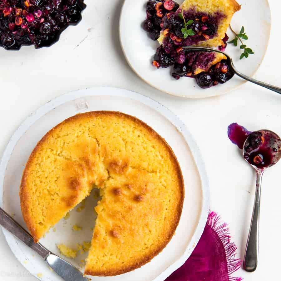 Round corn cake with a slice removed. Slice on white plate topped with blueberry compote.
