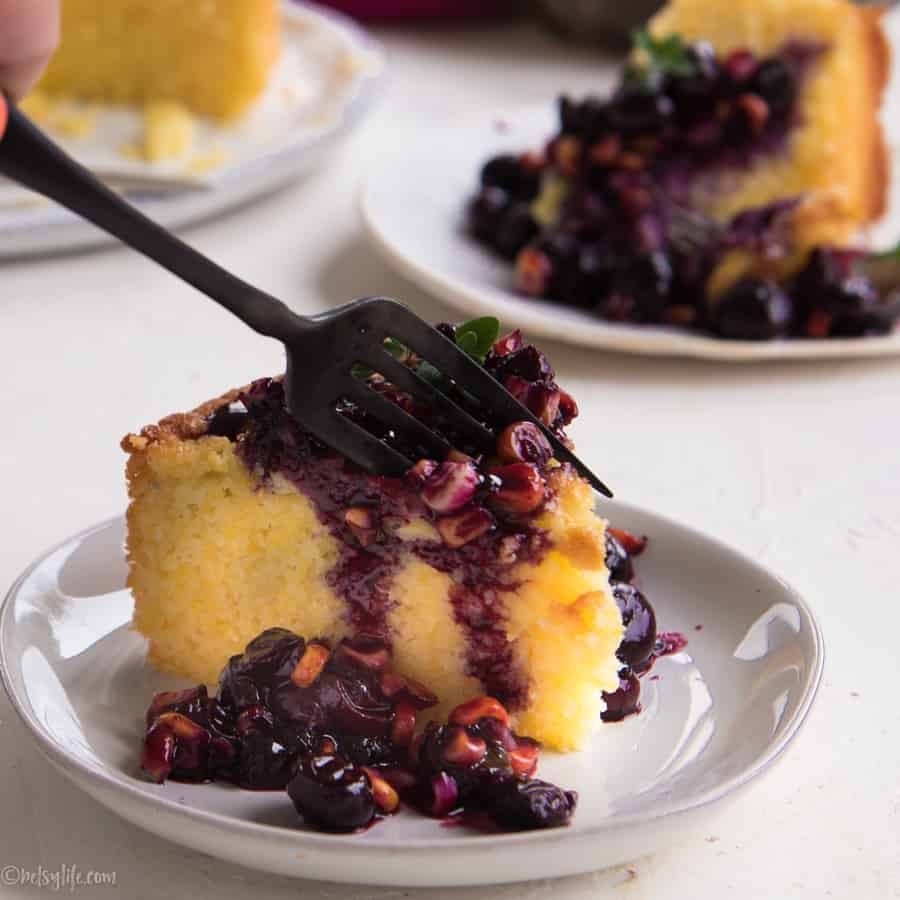 Slice of corn cake with blueberry compote with fork taking a bite
