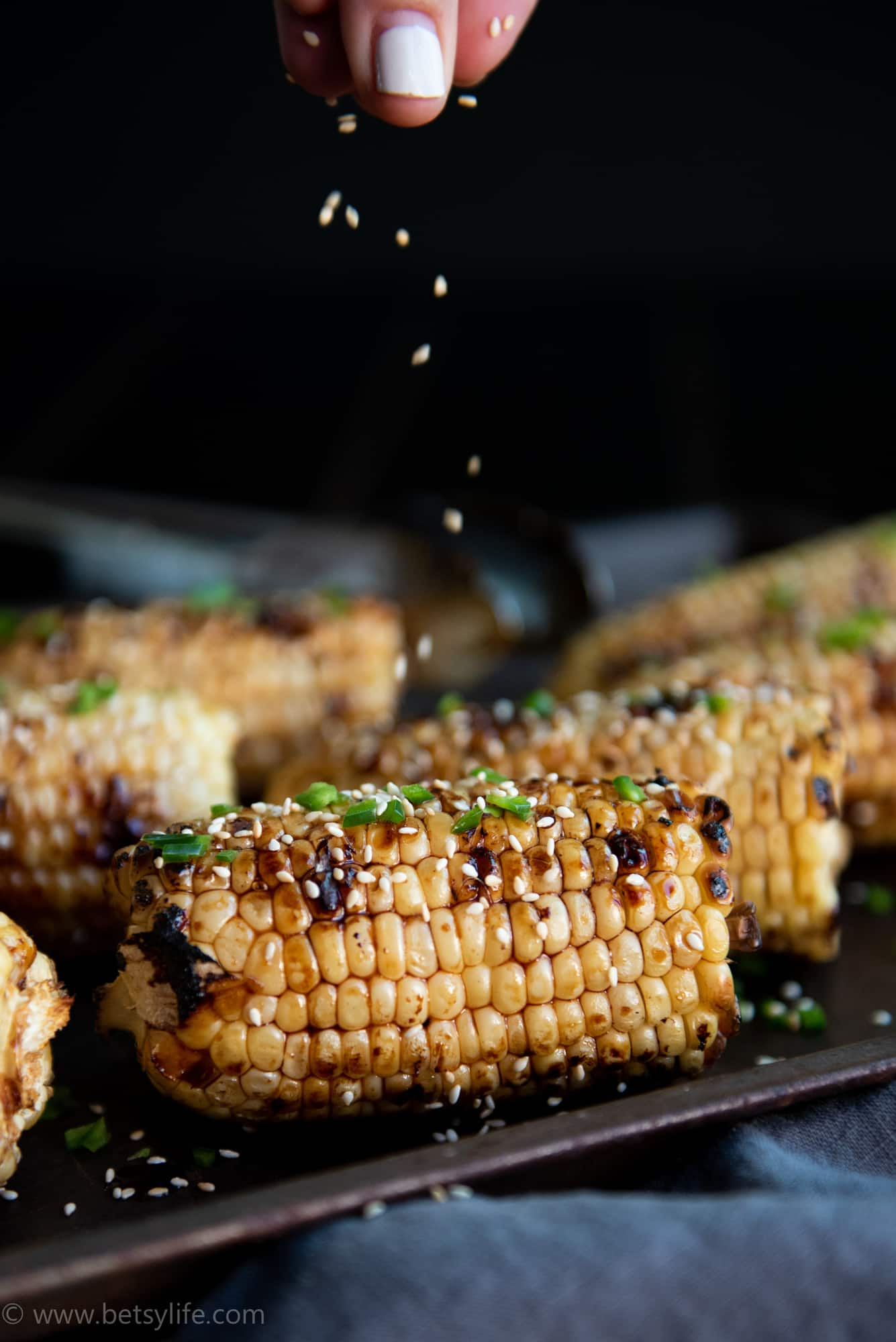 Sesame seeds being sprinkled on grilled corn on the cob