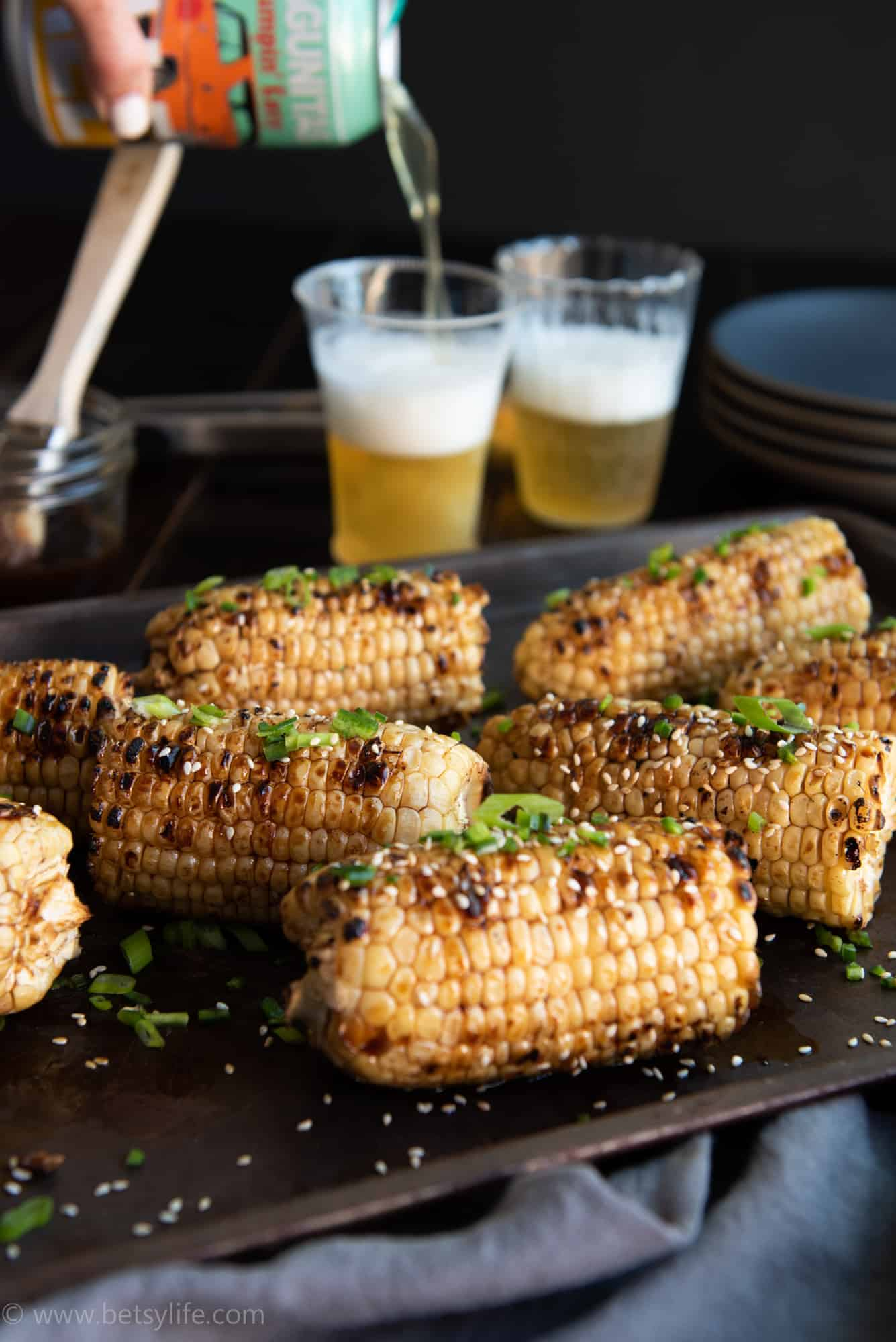 sesame glazed corn on the cob garnished with green herbs on a baking sheet. Beer being poured into glasses in the background