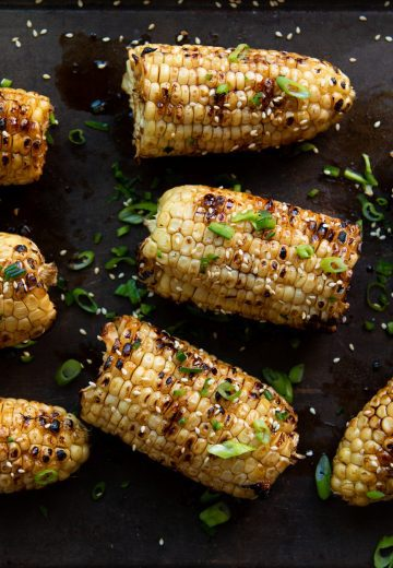 Grilled corn on the cob garnished with lime wedges, sesame seeds and green herbs on a baking sheet with glasses of beer