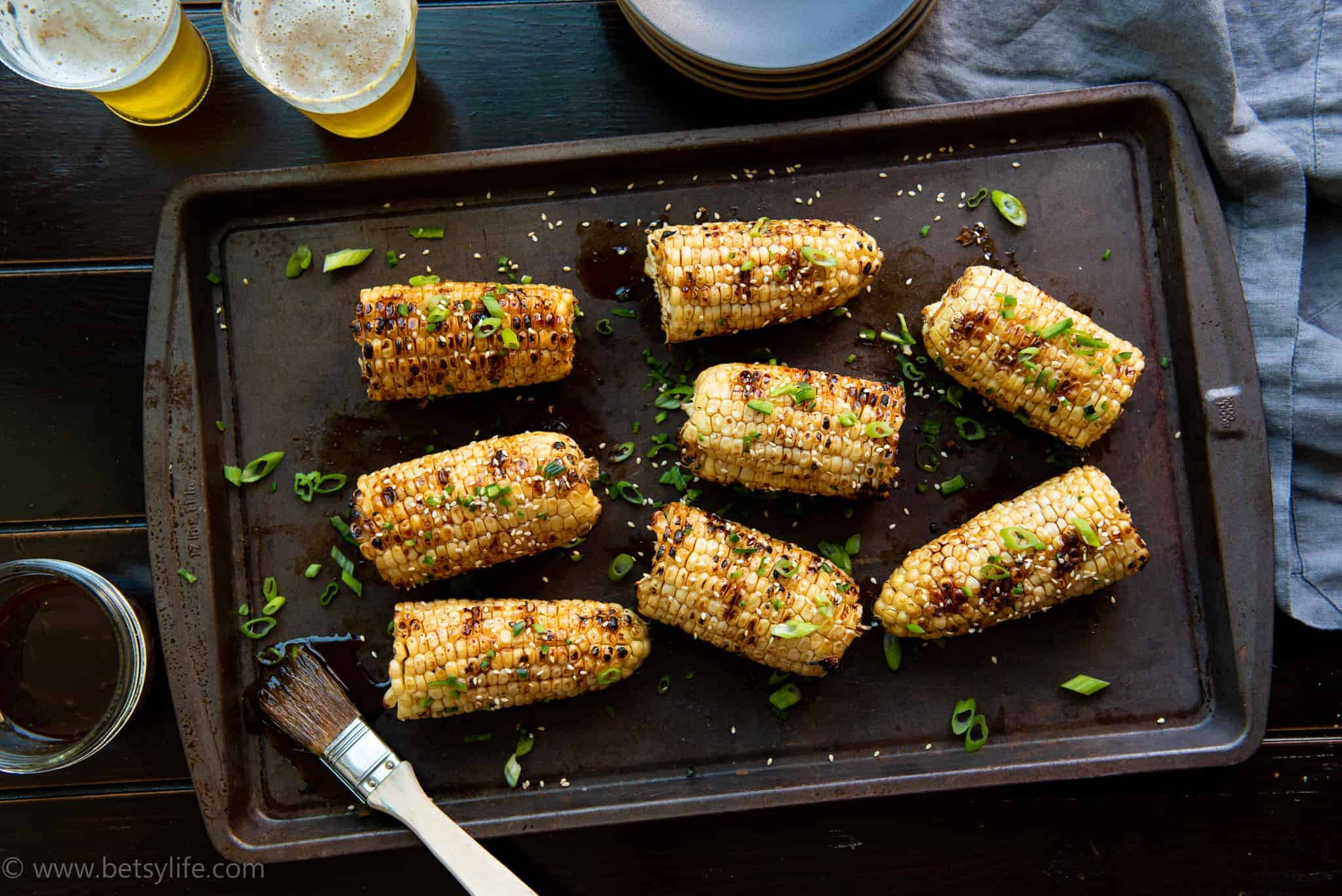 grilled sesame glazed corn on the cob on a baking sheet with green herb garnish