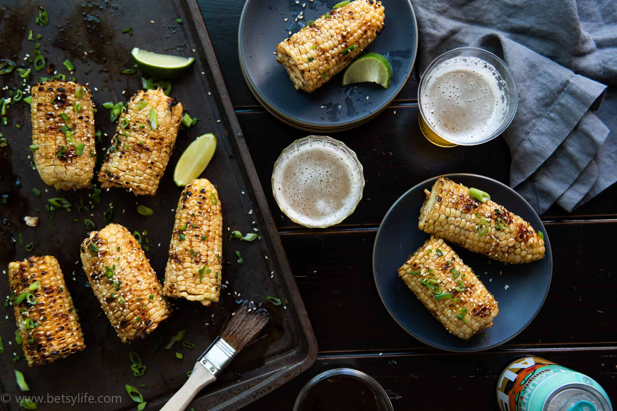 Table with tray of sesame glazed corn on the cob with two dark plates with corn servings and two beers