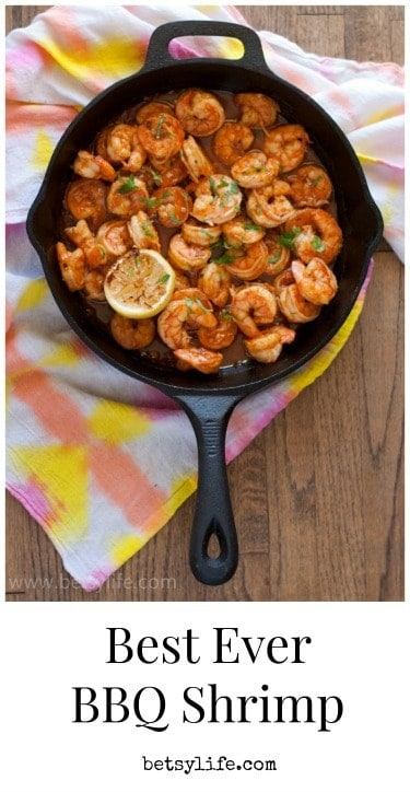 Overhead cast iron skillet filled with BBQ shrimp and grilled lemon halves on a pink and yellow tie dyed napkin