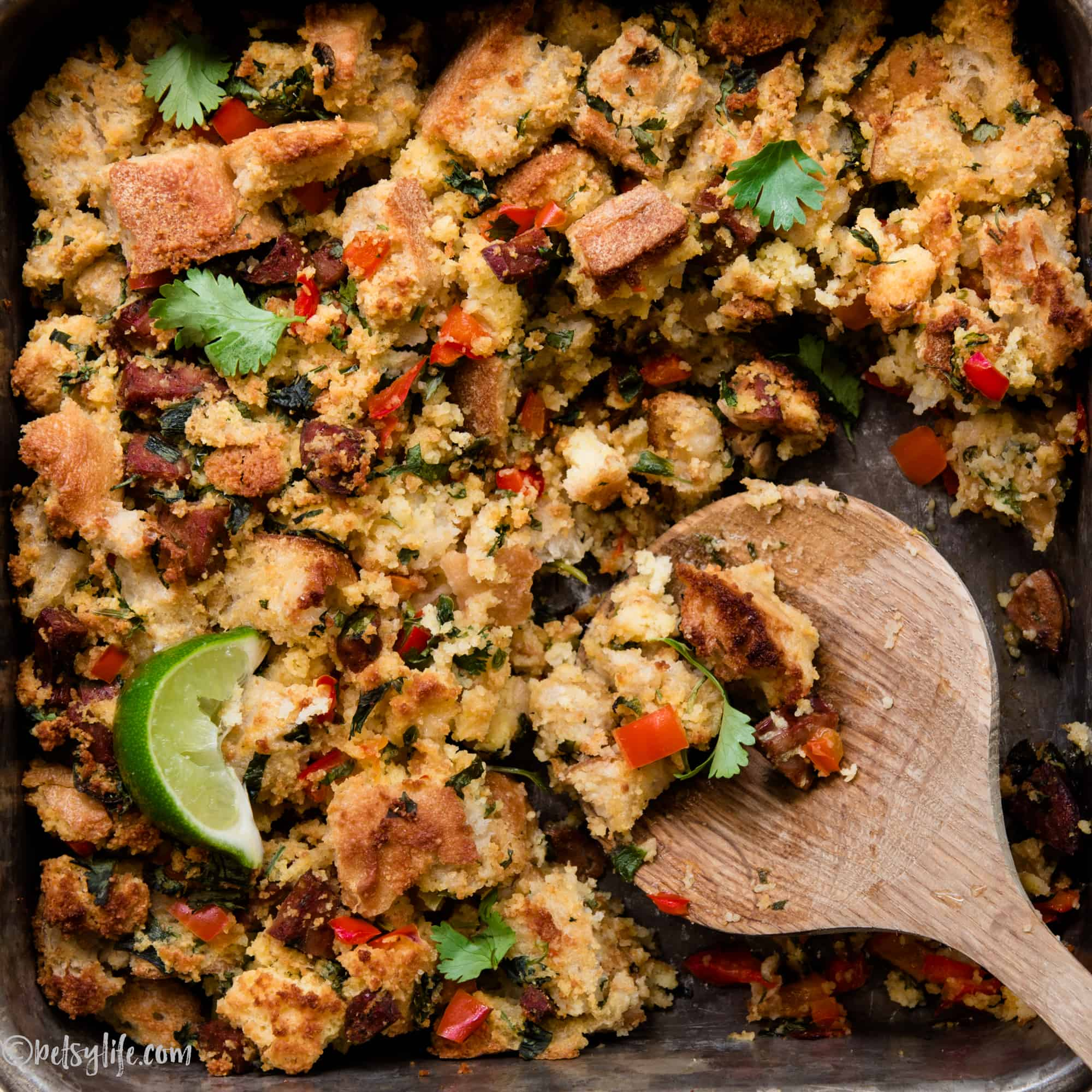 close up of cornbread, sausage stuffing with a wooden spoon