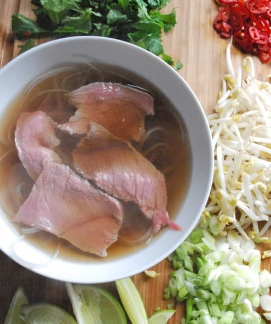 sliced beef in broth surrounded by vegetables