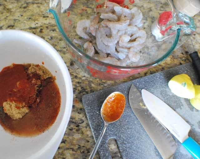 Overhead photo of raw shrimp in a glass bowl, a white bowl filled with bbq sauce and a cutting board with knives and sliced lemons