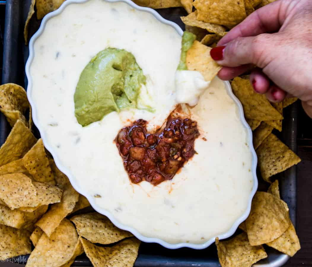 oval bowl of white cheese dip topped with guacamole and salsa surrounded by chips. Single chip dipping in