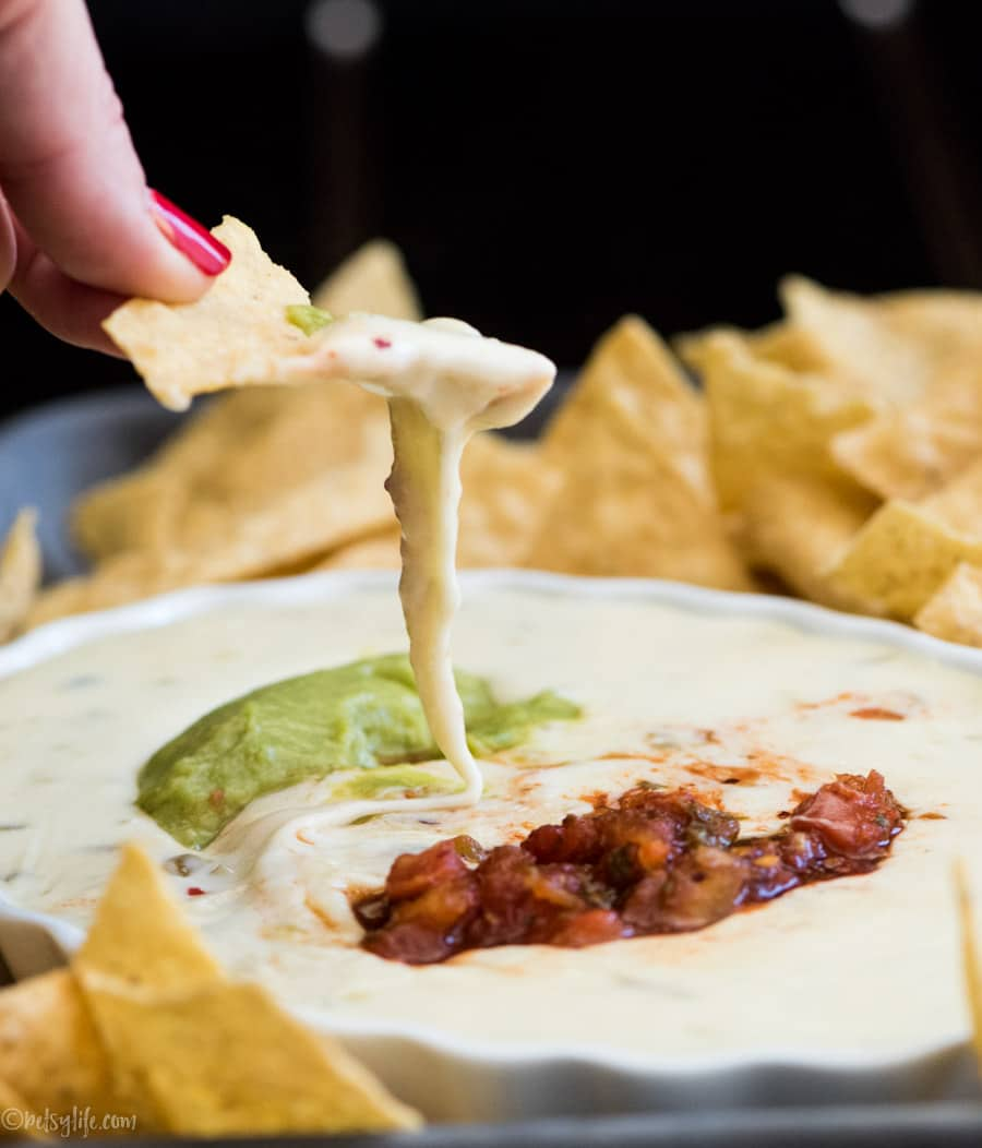 super easy queso blanco dip with a chip scooping out a serving.