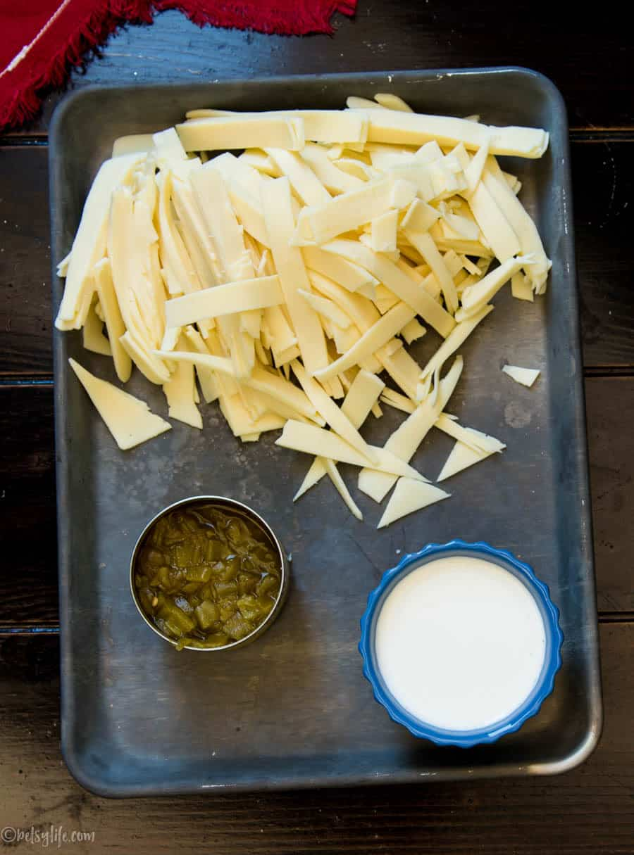 tray of ingredients for super easy queso blanco dip. Shredded american cheese, can of green chiles and cup of heavy cream