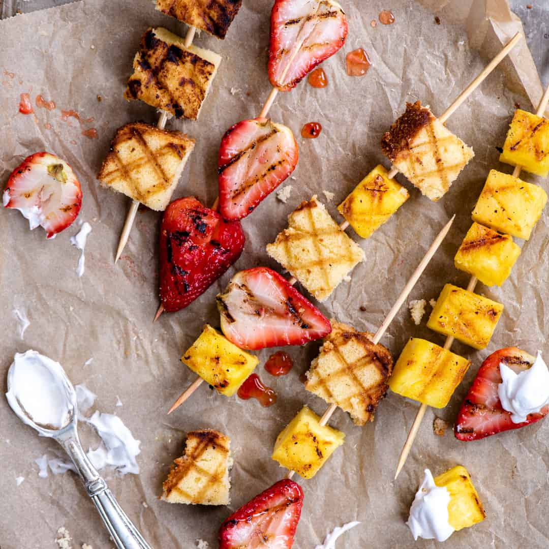 Grilled shortcake skewers with a spoon of whipped cream on a brown paper background