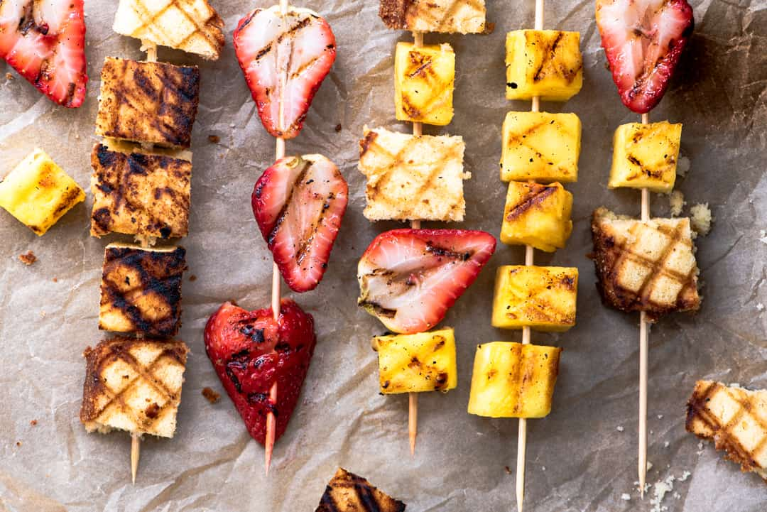 Detail of bbq skewers with grilled strawberry, pineapple and pound cake