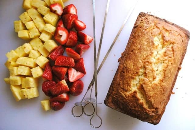 Loaf of pound cake next to diced strawberries and pineapple and Bbq skewers