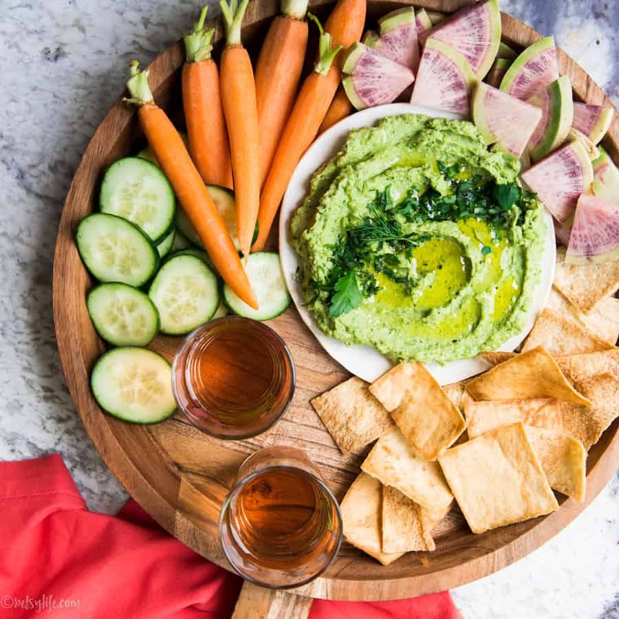 green pea hummus on a round wooden platter surrounded by veggies and pita chips with two glasses of wine