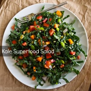 white plate piled with colorful kale salad