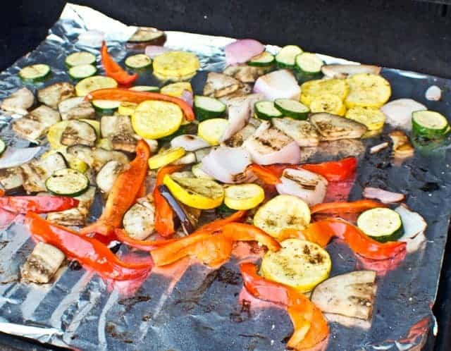 vegetables being cooked on foil on a grill
