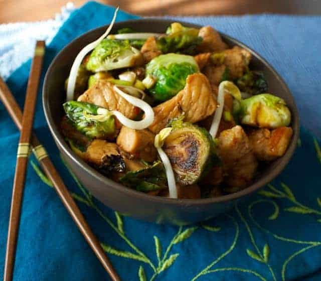 Pork and Brussels Sprout Stir Fry  in dark bowl with chopsticks