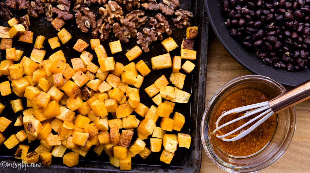 roasted squash and walnuts on a sheet pan next to a skillet of black beans and a small bowl of dressing with a whisk