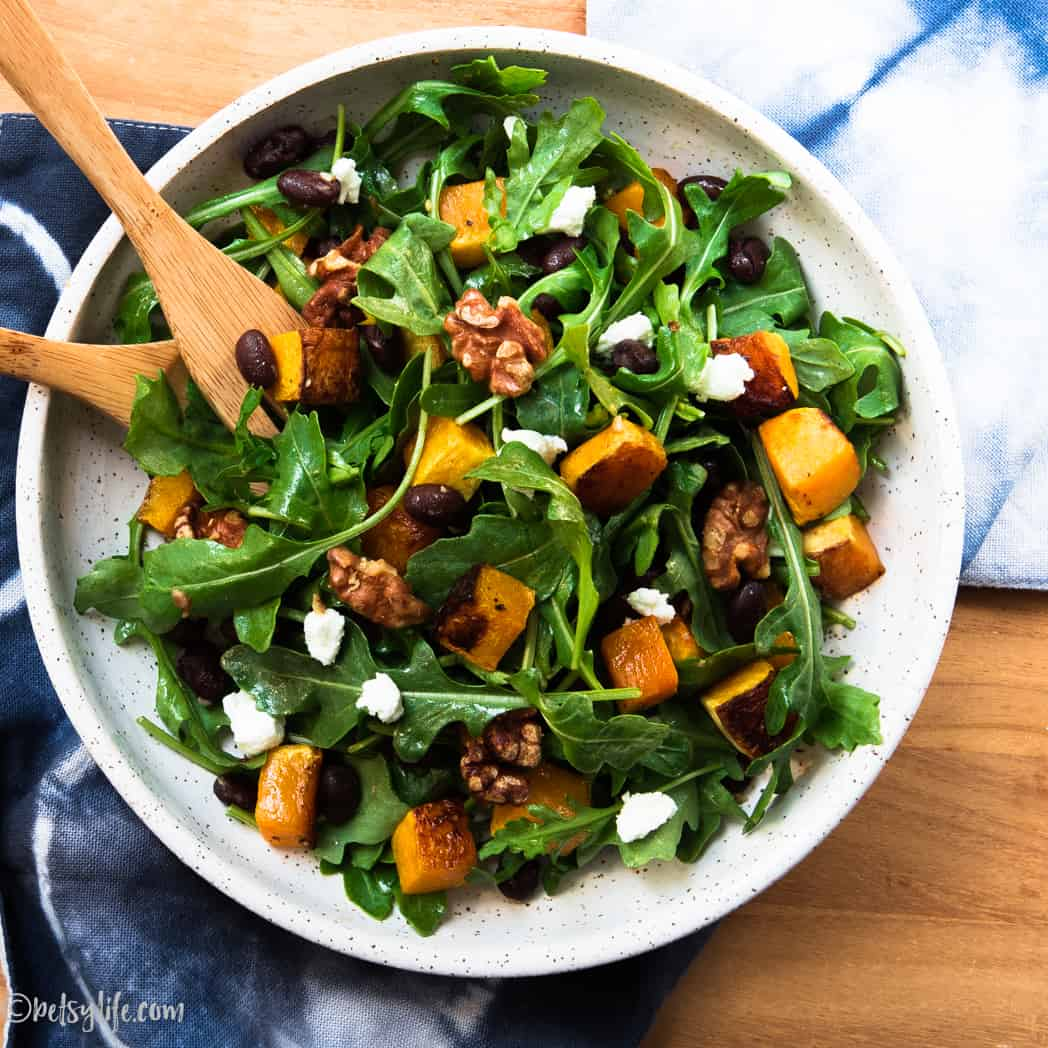 butternut squash, arugula, black bean, goat cheese salad in a round bowl