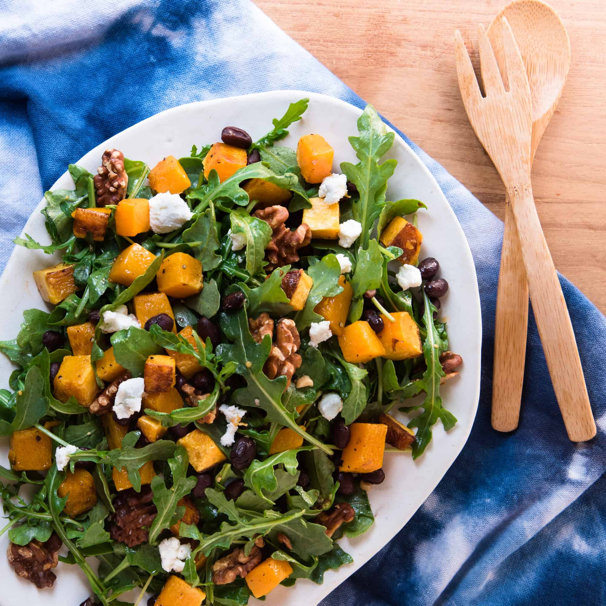 butternut squash salad with goat cheese, arugula, and walnuts on a blue linen with wooden serving spoons