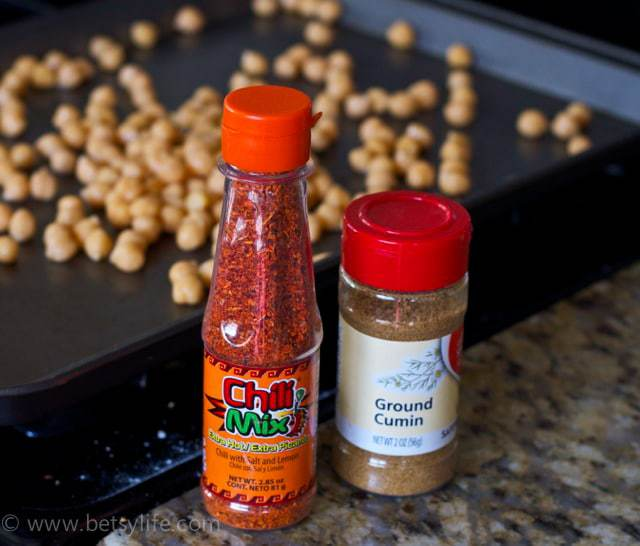 bottle of chili powder and cumin with chickpeas in background