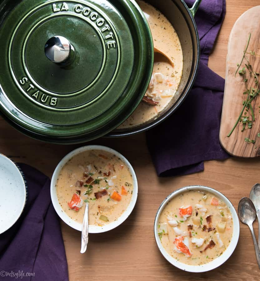 green dutch oven next to two bowls of lobster chowder