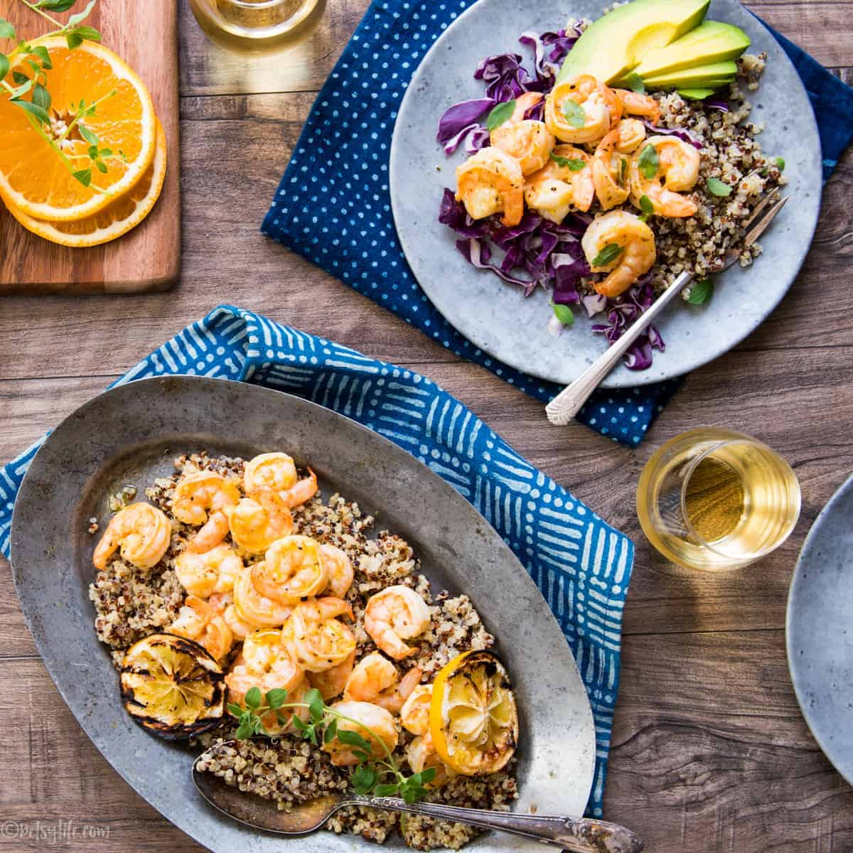 gray plate with a serving of orange shrimp, quinoa and cabbage next to a metal serving dish with the same ingredients. Two glasses of white wine and two blue napkins