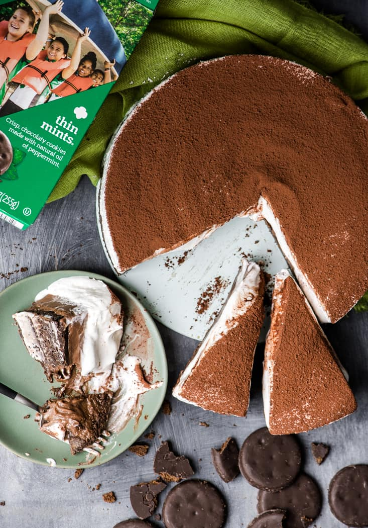 Partially eaten pie slice on a plate with a fork next to box of Girl Scout cookies, thin mints and chocolate pie with slices cut