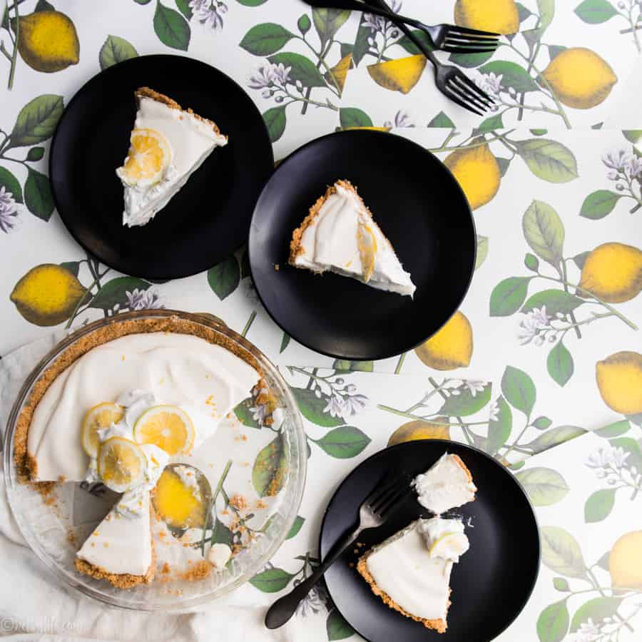 three slices of lemon cool whip pie on black plates next to pie in pan on a lemon print background