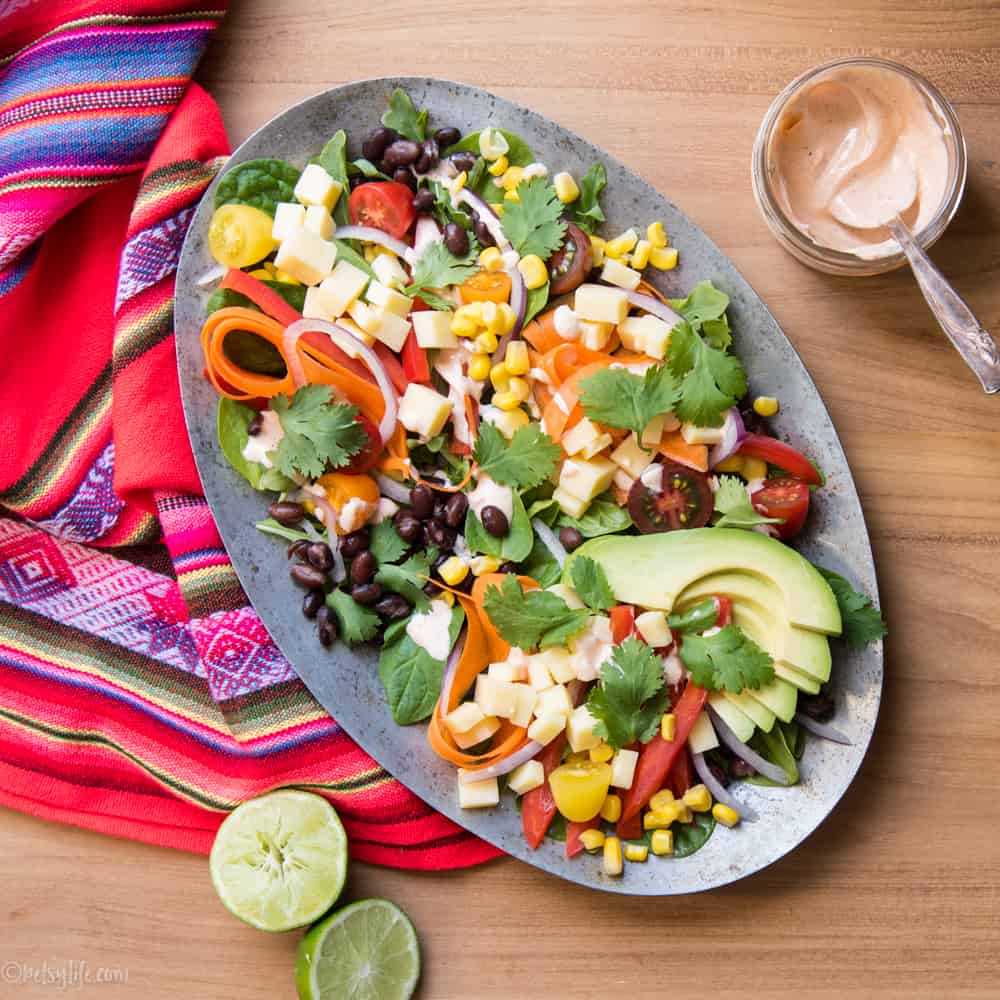 southwestern salad on a metal oval plate next to a jar of creamy dressing and a printed linen