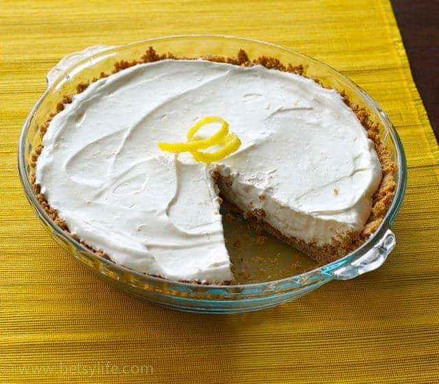 4 Ingredient Lemon Cream Pie on a yellow placemat. One slice removed