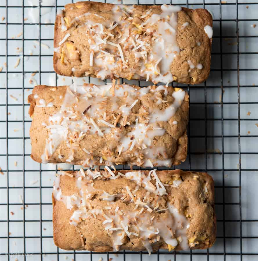 three mini loaves of guava bread on a cooling rack topped with toasted coconut