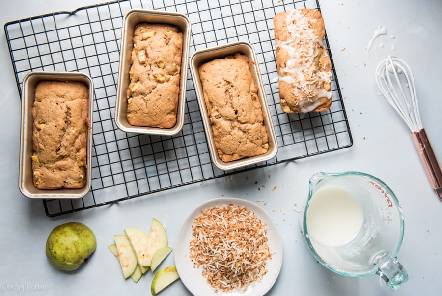 4 mini loaves of guava bread next to a plate of toasted coconut, a measuring cup of glaze and a sliced guava