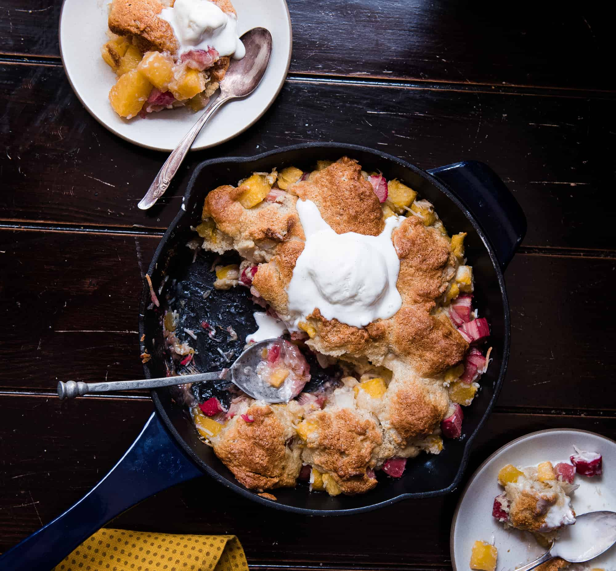 Skillet full of rhubarb pineapple cobbler next to two servings on white plates
