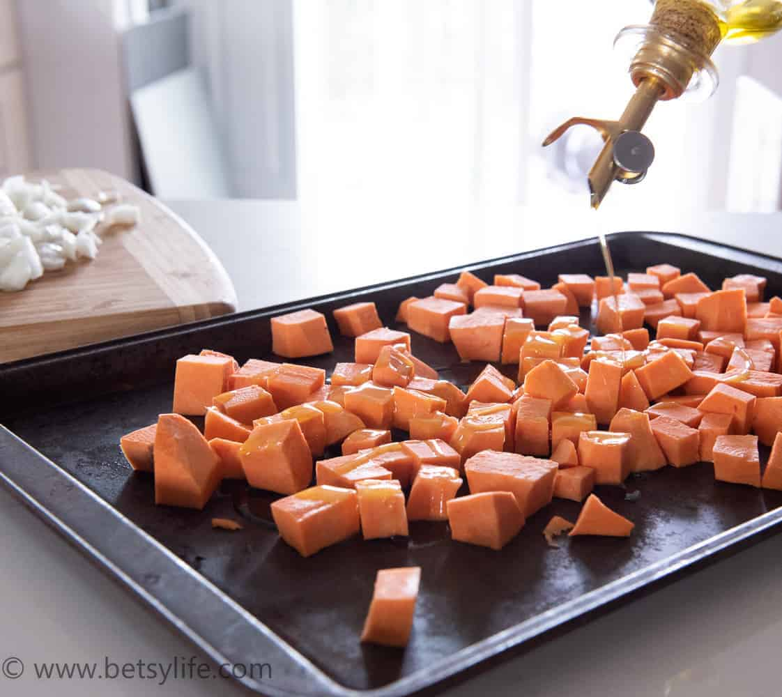 diced sweet potatoes on a baking sheet being drizzled with oil