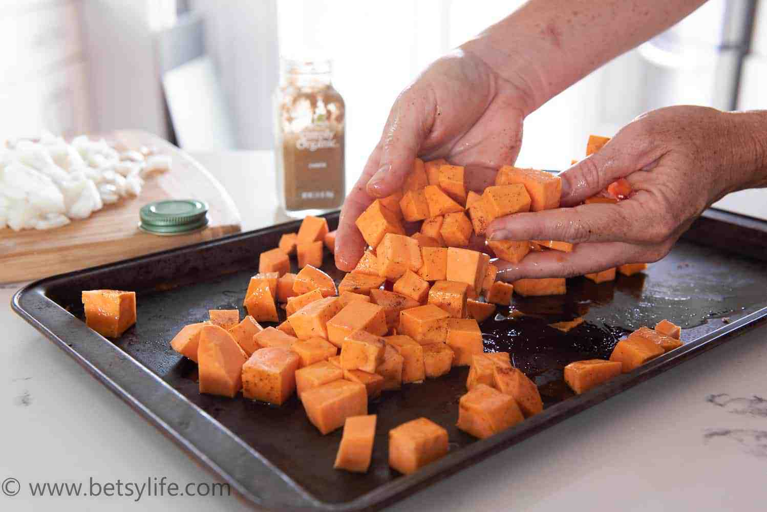diced sweet potatoes being tossed on a baking sheet with oil and spices