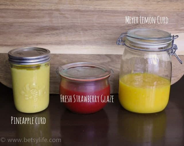 3 mason jars. One filled with something yellow and is labeled pineapple curd. One is full of something red and is labeled fresh strawberry glaze. The final one is filled with something darker yellow and is labeled Meyer lemon curd