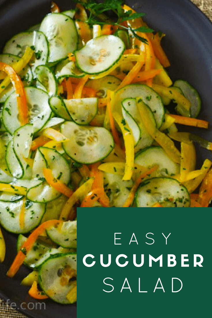 Easy Cucumber Salad. Thinly sliced cucumbers, orange and yellow peppers and fresh herbs on a dark oval serving platter