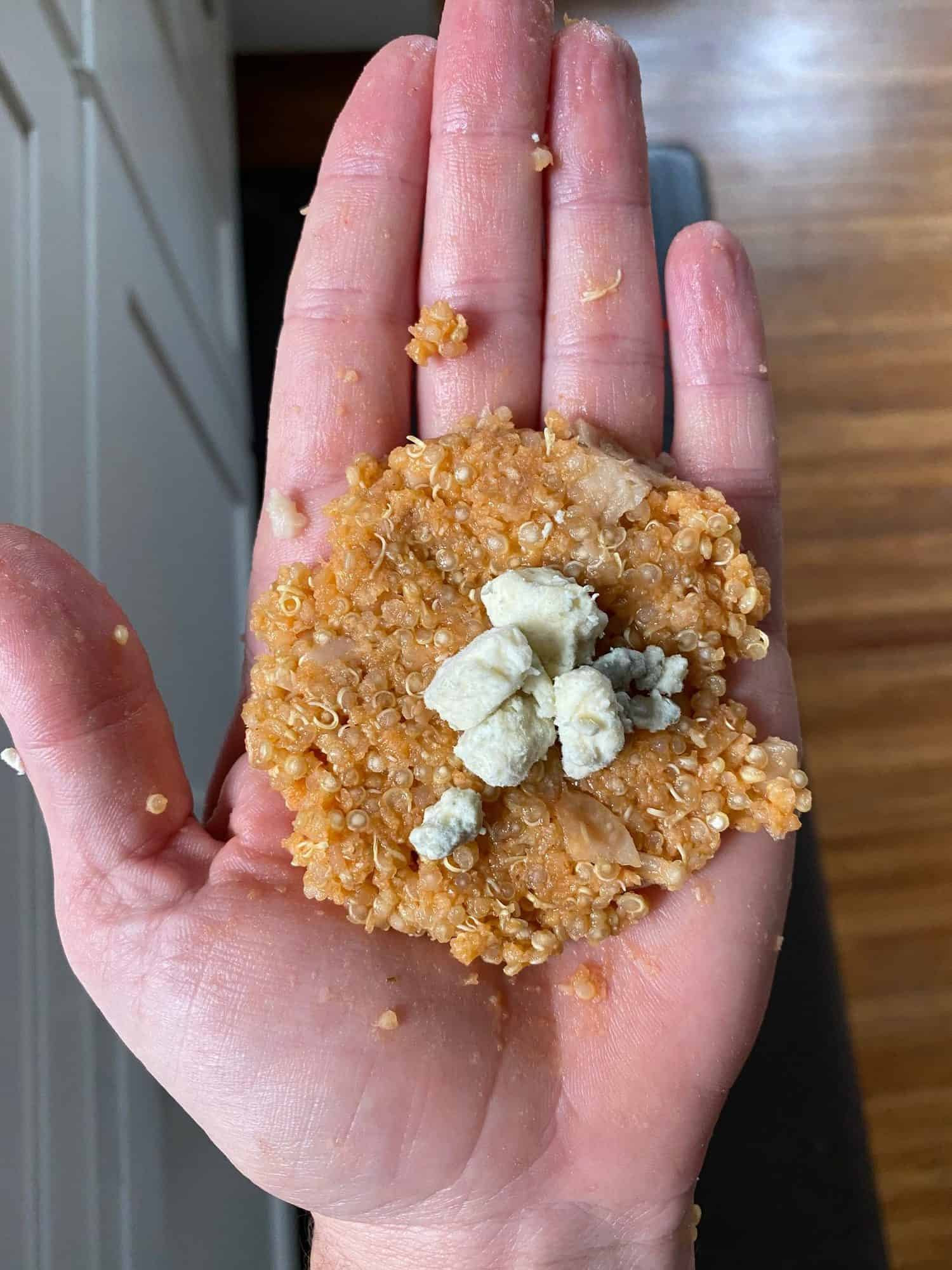 hand holding a patty of quinoa mix with blue cheese crumbles in the center