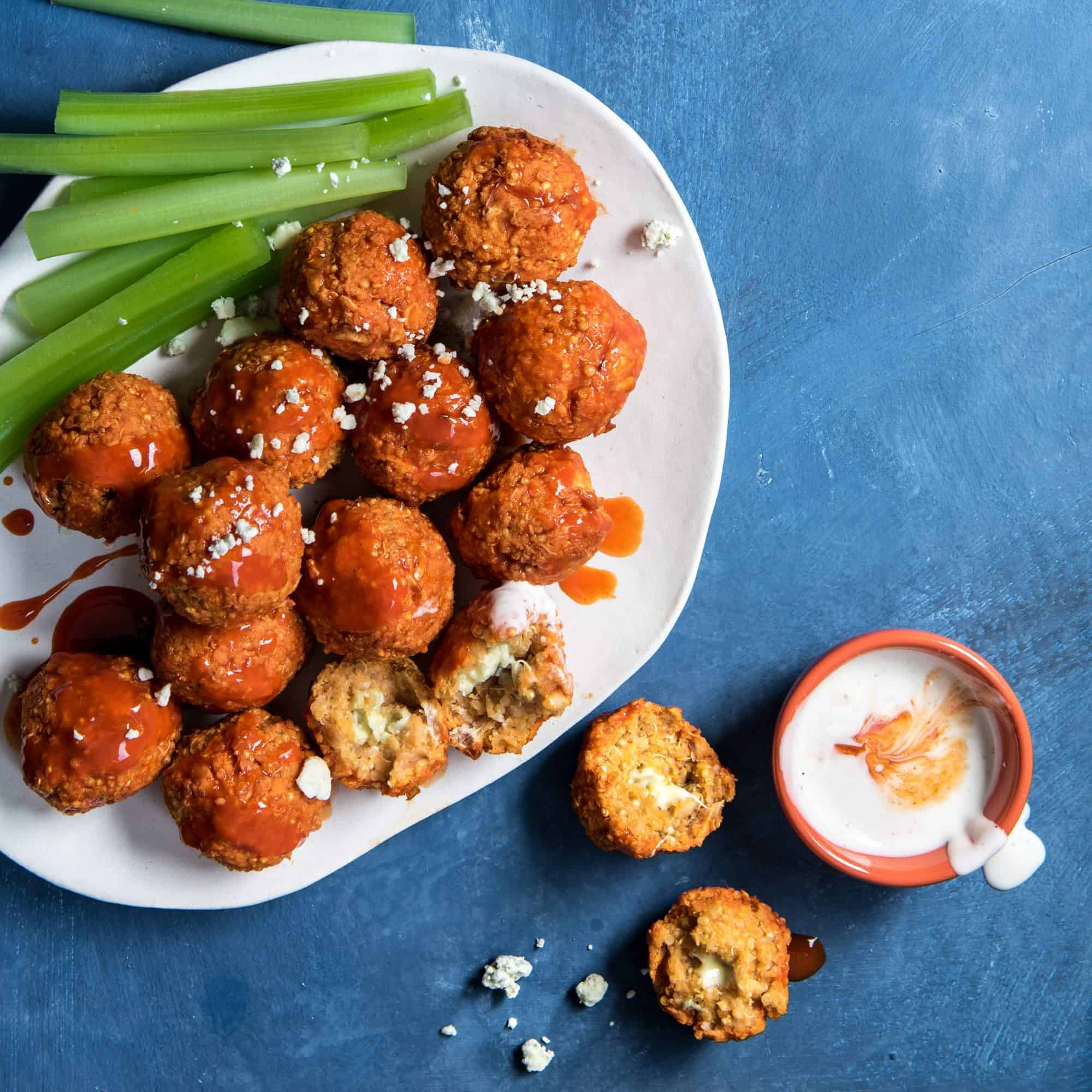 White plate of buffalo quinoa bites and celery on a blue background next to a bowl of white dipping sauce