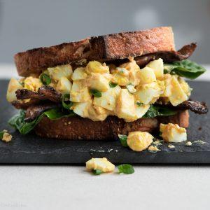 Profile close up of a sriracha bacon egg salad sandwich
