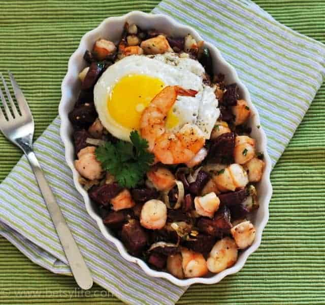 Shrimp and Sweet Potato Hash with fried egg in oval plate on green napkin